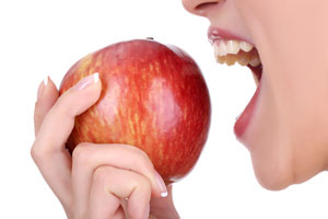 a woman about to bite an apple